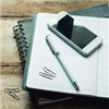 Image of notebook, phone and pencil
