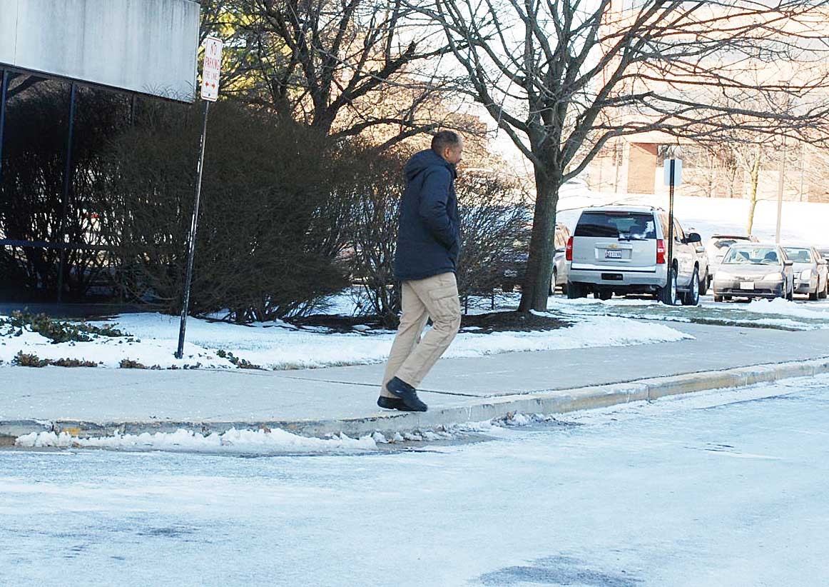 Man walking on sidewalk that has been shoveled with snow on grass.