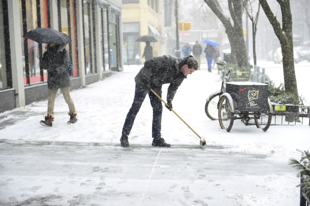 Man Brushing the Snow Off the Sidewalk