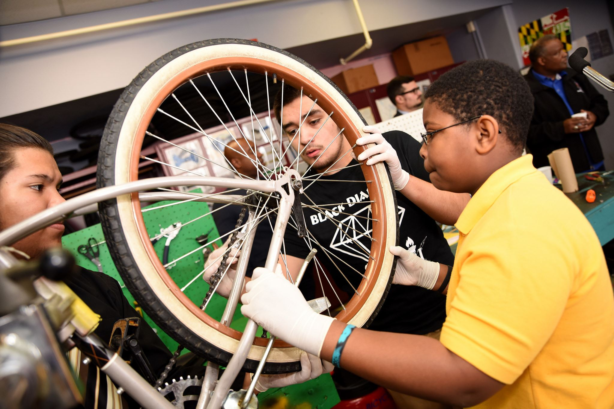 Three Students Working on a Bicycle Wheel